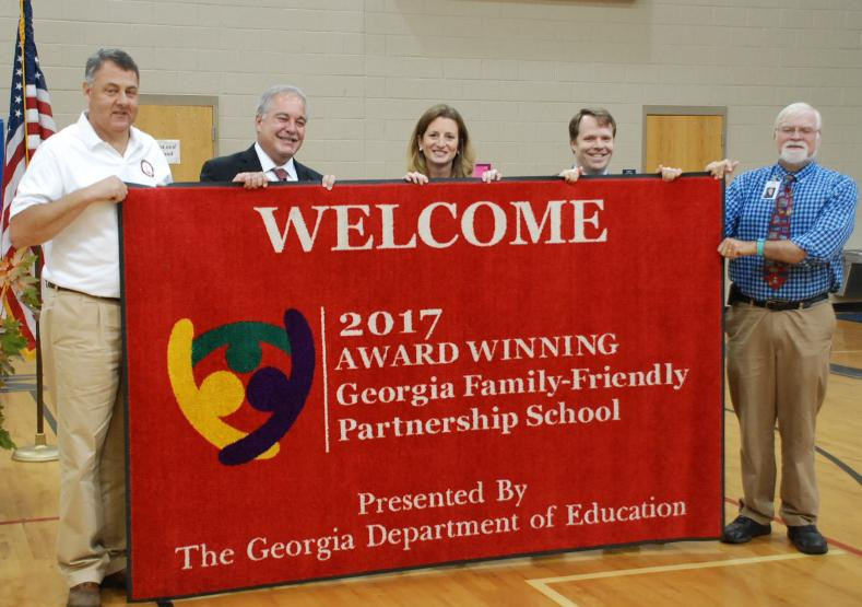 Displaying the Family Friendly Partnership School door mat L-R  State Senator Steve Gooch, Richard Woods, Principal Jennifer King, DOE Communication Specialist Jason Clay, and White County Superintend of Schools Dr. Jeff Wilson