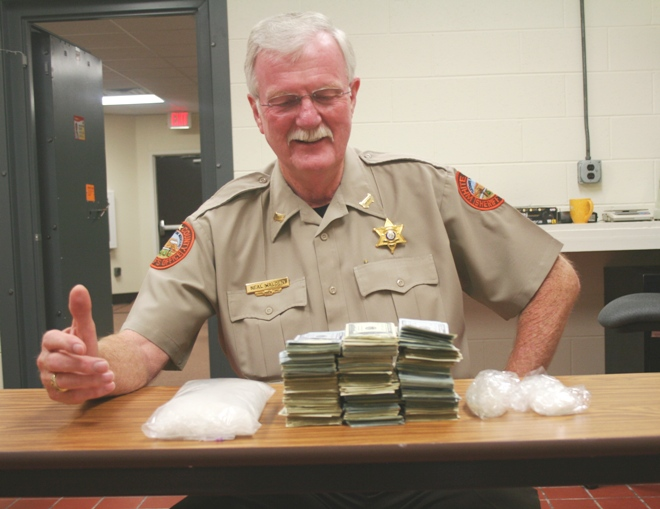 White County Sheriff Neal Walden looks at the pile  of loot confiscated in drug bust Monday